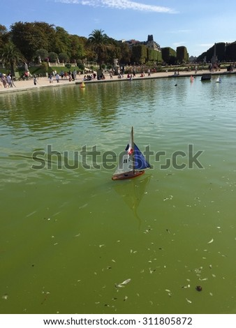PARIS - AUGUST 29: Unknown children playing with countries flagged boats on small lake, Luxembourg Gardens, Paris, France on 29 August 2015 - stock photo