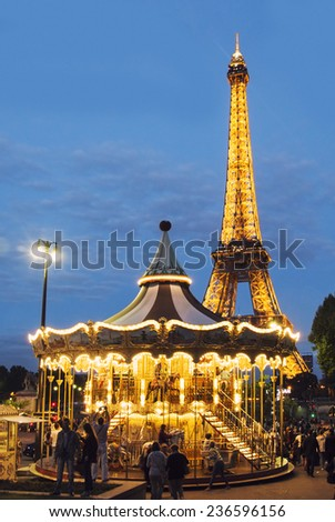 PARIS - August 21: Vintage merry-go-round at night with the illuminated Eiffel Tower in the background on August 21, 2014 in Paris.