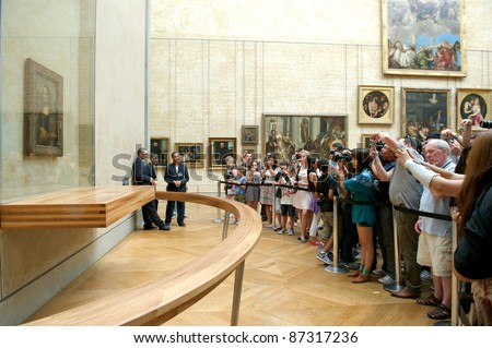 """PARIS - AUGUST 4: Visitors take photo of Leonardo DaVinci's """"Mona Lisa"""" at the Louvre Museum, August 4, 2011 in Paris, France. The painting is one of the world's most famous. - stock photo"""