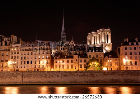 Paris by night: ile de la cit�© with side view of Notre Dame cathedral as seen from river Seine bank - stock photo