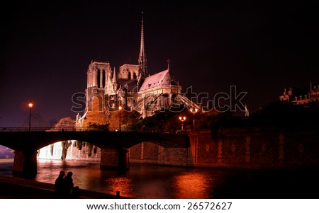 Paris by night: Notre Dame cathedral as seen from river Seine bank - stock photo