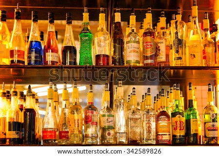 PARIS - Dec 23, 2013: Bottles of alcohol and spirits on backlit shelves at a pub or bar. Variety of French and imported labels. - stock photo