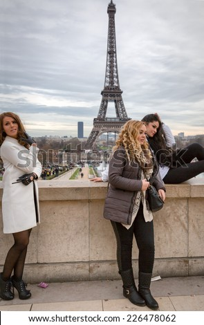 PARIS-DEC 31,2013: Women posing for pictures with the Eiffel Tower in the background.This spot at the Esplanade du Trocadero has the best view of the iconic landmark and attracts huge crowds daily. - stock photo