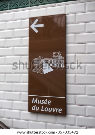PARIS - DECEMBER 16: A sign posted at a Paris Metro entrance points the way to The Louvre museum on December 16, 2015 in Paris, France. The Louvre is one of the most visited art museums in the world. - stock photo