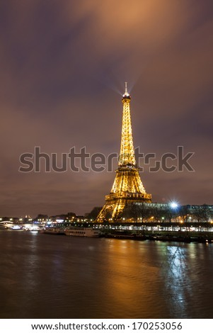 PARIS - DECEMBER 27: Eiffel Tower and river Seine at night on December 27, 2013 in Paris. The Eiffel tower is the most visited monument of France with about 6 million visitors every year.