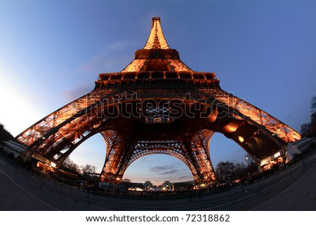 PARIS - DECEMBER 23: Eiffel Tower at twilight on December 23, 2009 in Paris. The Eiffel Tower stands 324 meters (1,063 ft) tall. - stock photo