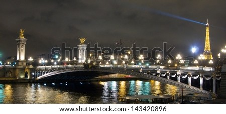 PARIS - DECEMBER 20: Paris at night with the Eiffel Tower in the background  on December 20, 2009. The Eiffel tower is the most visited monument of France with about 6 million visitors every year. - stock photo