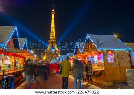 PARIS - DECEMBER 16, 2013: The Christmas market at the Trocadero gardens. The Eiffel Tower in the background projects the colors of the South African flag as a tribute to Nelson Mandela. - stock photo