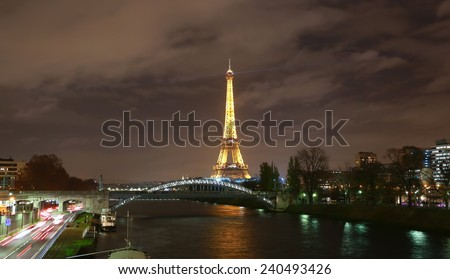 PARIS - DECEMBER 11: The illuminated Eiffel Tower in the night on Dec. 11, 2014 in Paris, France.The Eiffel tower is most visited monument of France with 6 million visitors every year . - stock photo