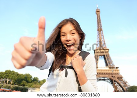 Paris Eiffel tower tourist happy backpacking in Europe. Cheerful smiling woman tourist showing thumbs up success sign in front of Eiffel Tower, Paris. Beautiful Asian Caucasian female model. - stock photo