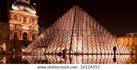 PARIS - FEBRUARY 28: An unidentified man walks by the glass pyramid at Louvre on February 28, 2009 in Paris. - stock photo