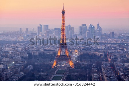 PARIS - FEBRUARY 7: Eiffel Tower brightly illuminated at dusk on FEBRUARY 7, 2015 in Paris. The Eiffel tower is the most visited monument of France.