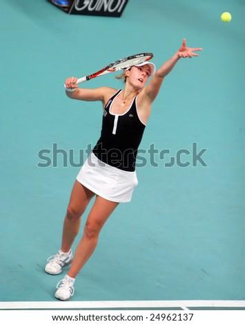 PARIS - FEBRUARY 13: French tennis player Alize Cornet serves during her quarter final match at Open GDF SUEZ WTA tournament, Pierre de Coubertin stadium on February 13, 2009 in Paris, France. - stock photo