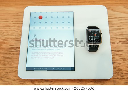 PARIS, FRANCE -  APR 10, 2015: New wearable computer Apple Watch smartwatch displaying the new Calendar App. Apple Watch incorporates fitness tracking and health-oriented capabilities with iOS