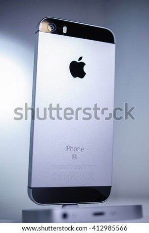 PARIS, FRANCE - APR 21, 2016: Rear view of the new Apple iPhone SE in docking station combining the updated processor, 4K rear camera, touch id, retina display - stock photo