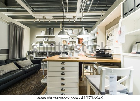 PARIS, FRANCE - APR 12, 2016: Woman choosing modern kitchen furniture and kitchen appliances in the modern IKEA shopping furniture mall in Paris