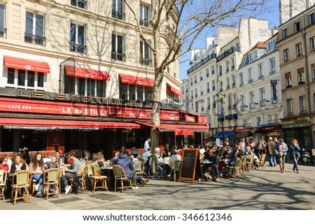 PARIS, FRANCE - APRIL 6, 2015: Parisians and tourists sit on Le Bastille terrace. This popular cafe, ideal place for people watching, located at Place de la Bastille opposite Opera Bastille building.