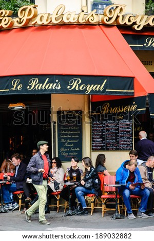 PARIS, FRANCE - APRIL 20, 2014: Parisians and tourists sit on the terrace of Palais Royal. This popular cafe, ideal place for people watching, is located near Palais Royal and Louvre museum. - stock photo