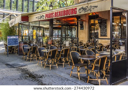 PARIS, FRANCE - APRIL 24, 2015: Street view of a typical outdoor coffee terrace with tables and chairs near Centre Georges Pompidou. - stock photo