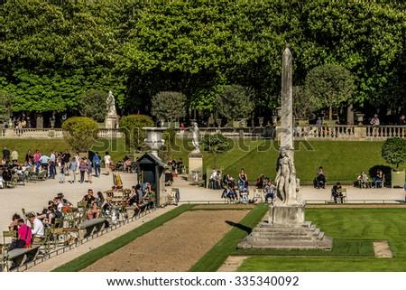 PARIS, FRANCE - APRIL 23, 2015: Tourists and Parisians relaxing in Luxembourg Garden (Jardin du Luxembourg). Jardin du Luxembourg - second largest Public Park in Paris. Park is garden of French Senate - stock photo