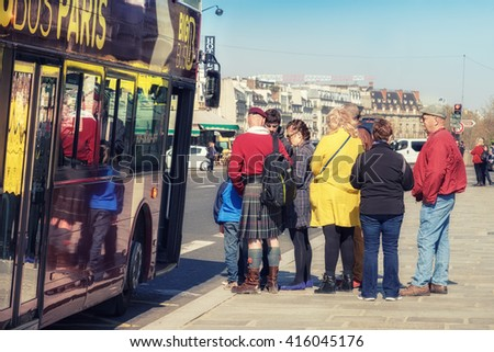 PARIS, FRANCE - APRIL 20, 2016: Tourists board sightseeing bus in Paris City Senter. Paris is one of the most visited cities in the world. This image is toned. - stock photo