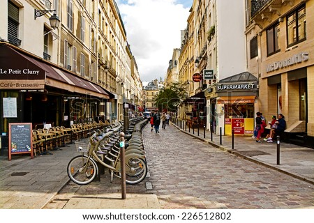 PARIS, FRANCE - August 18, 2014: Latin Quarter of Paris, France. Narrow street of Paris among old traditional parisian houses and cafe in Paris. - stock photo
