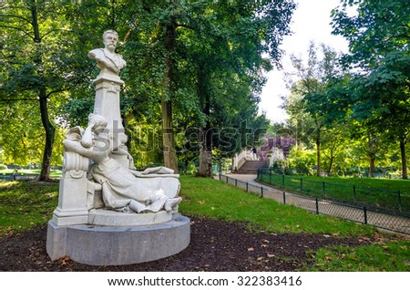 PARIS, FRANCE - AUGUST 28, 2015: Monceau Park is one of the most beautiful in the city with dozens of white marble statues of famous French celebrities including novelist and poet Guy de Maupassant.  - stock photo