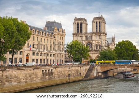 Paris, France - August 07, 2014: Notre Dame de Paris cathedral. The most popular city landmark with people walking on Seine river embankment - stock photo