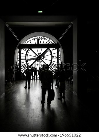PARIS, FRANCE - AUGUST 25 2013: Silhouettes of tourists visiting d'Orsay Museum shot against big external clock - stock photo