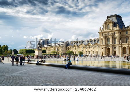 PARIS, FRANCE - AUGUST 13, 2014: The view of the Napoleon yard and the Louvre. The Louvre Museum is the world's most visited museum and popular tourist attraction of Paris. - stock photo
