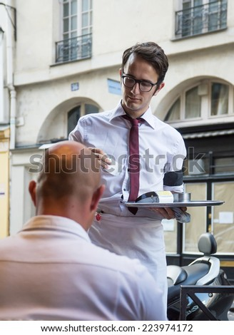 PARIS, FRANCE - August 06, 2013 : Waiter serving customers at traditional outdoor Parisian cafe in center city. - stock photo