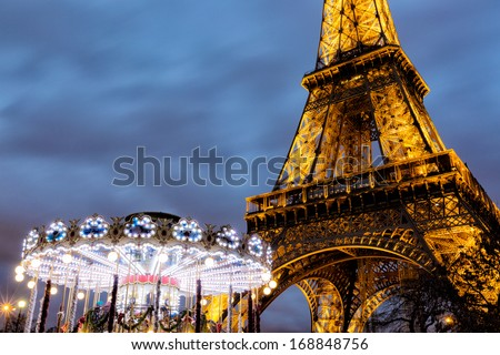 PARIS, FRANCE - DEC. 27, 2013: The Eiffel Tower and a carousel brightly illuminated in evening light. Two iconic and familiar symbols of life in Paris. Copy space. - stock photo
