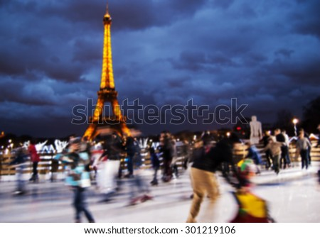 PARIS, FRANCE - DECEMBER 29, 2012: Blurred defocused illuminated Eiffel Tower and people on ice rink. Eiffel tower is the most visited paid monument in the world with over 7 million visitors a year. - stock photo