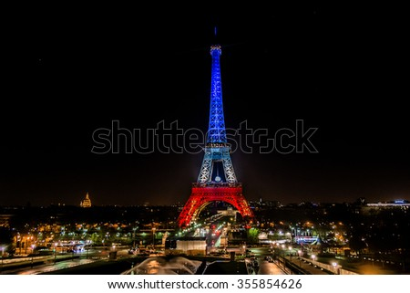 PARIS, FRANCE - DECEMBER 16, 2015: Eiffel tower illuminated with colors of French national flag to honor the victims of November 13 Friday's terrorist attacks. - stock photo