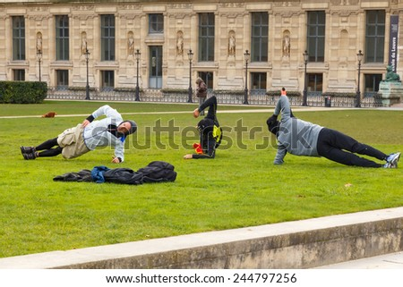 Paris, France - December 20, 2014: Group of men athletes involved in sports on the lawn in the garden of the Tuileries. - stock photo