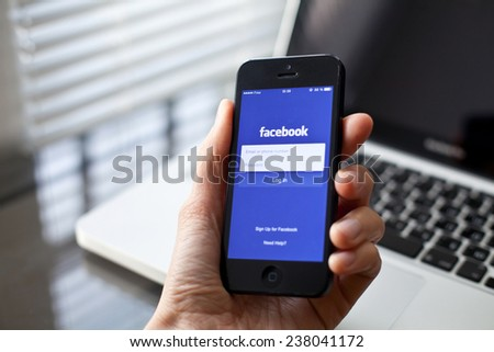 Paris, France - December 11, 2014: Hand holding Iphone with mobile application for Facebook on the screen, laptop on background