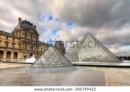 PARIS, FRANCE - FEBRUARY 19, 2014: Beautiful view of the Louvre pyramids on a cloudy winter day in Paris, France, on a cloudy day in February, 2014 - stock photo