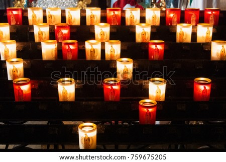 PARIS, FRANCE - FEBRUARY 1, 2017: Rows of firing lit votive candles inside Notre Dame de Paris, France.