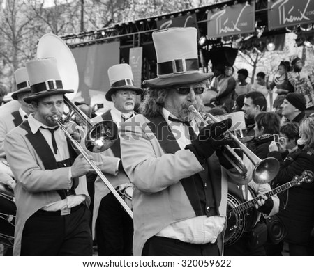 PARIS, FRANCE - JANUARY 1, 2015: Brass band in vintage tuxedos participates in the New Year Parade on  Avenue des Champs-Elysees. Colorful New Year Parade is annual event.