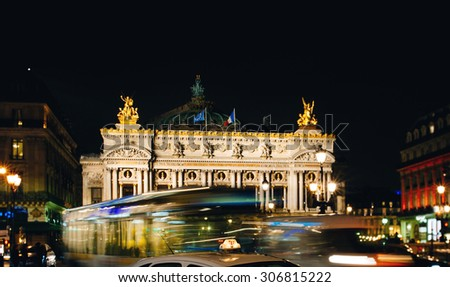 PARIS, FRANCE - JANUARY 22, 2013: City Bus and Taxi passing in front of the Palais Garnier - Opera Garnier & The National Academy of Music -  illuminated at night in Paris, France