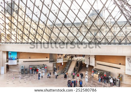 Paris, France - January 11, 2015: People are inside (visiting) the Louvre Museum. Pyramid is the main entrance of Louvre Museum. It is one of the largest and famous museums in the world. - stock photo