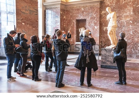 Paris, France - January 11, 2015: People are taking photo of Aphrodite of Milos at the Louvre Museum. Tourists are visiting (inside ) the museum. It is one of the largest museums in the world. Paris.  - stock photo