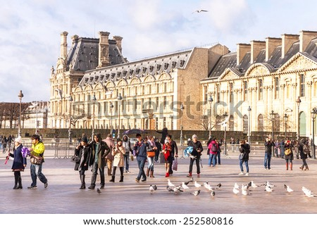 Paris, France - January 11, 2015: View of main courtyard of Louvre Museum in the sunny day. People are walking. Louvre Museum is one of the largest and famous museums in the world. Paris. Outdoor. - stock photo