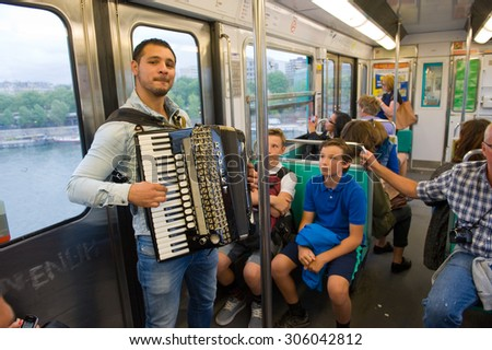 PARIS, FRANCE - JULY 28, 2015: A musician is playing accordion in the metro in Paris in France - stock photo