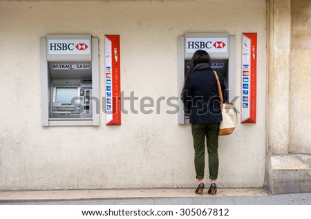 PARIS, FRANCE - JULY 28, 2015: A woman is withdrawing money from an ATM machine on a street in Paris in France. - stock photo