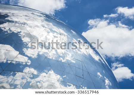 PARIS, FRANCE - JULY 21: Close up photo of La Geode in Parc de La Villette with reflections of the sky and clouds on July 21, 2015 in Paris, France