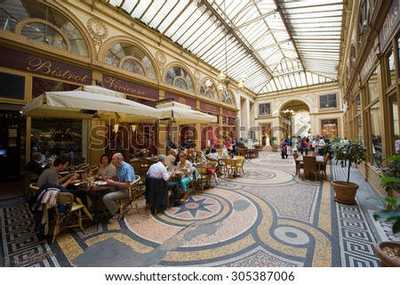 PARIS, FRANCE - JULY 27, 2015: Galerie Vivienne is an ancient historical passage with shops and restaurants and a tourist attraction in Paris in France - stock photo