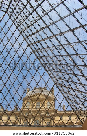 PARIS, FRANCE - JULY 4, 2015:  Louvre Museum showing glass pyramid from inside and building in the background in Paris, France on July 4, 2015 - stock photo