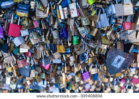 Paris, France - July 31, 2013 - Many Love locks on a bridge in Paris , symbol of eternal love and relationship, with romantic Seine river as background, Paris, France - stock photo
