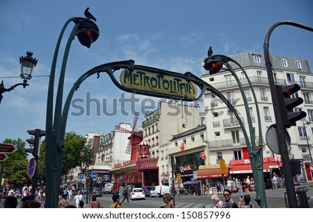 PARIS, FRANCE - JULY 24, 2013: The Famous Moulin Rouge Nightclub in Monmatre viewed through the wonderful Rail Station wrought iron on July 24, 2013 in Paris.